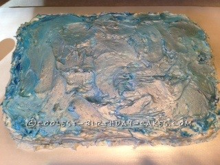 """This is the water...made by mixing blue glitter icing with the white buttercream icing to make """"waves""""."""